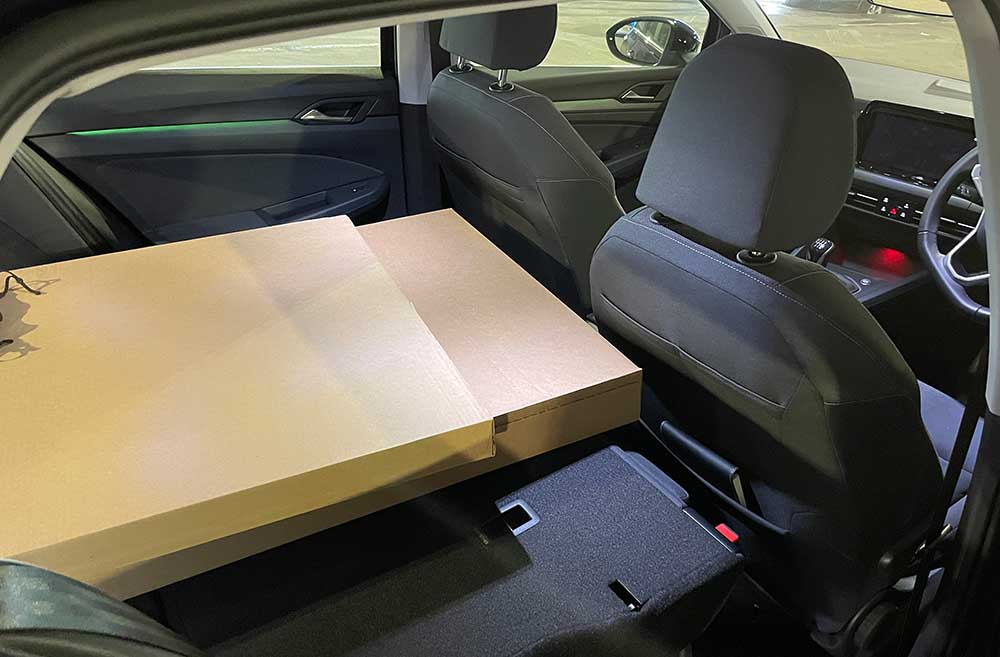 Photo of a large box inside the car, with the rear seats folded down.